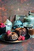 Kleine Schokoladennapfkuchen mit Schokoladen-Sauerrahm-Glasur und frischen Himbeeren