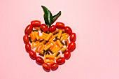 Verschiedene bunte Nudeln in einem Tomatenherz