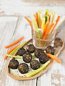 Vegan macadamia nut and cashew nut cheese balls rolled in nori and served with vegetable sticks