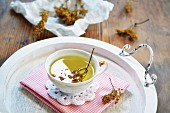 Elderflower tea in a teacup on a tray in front of dried elderflower