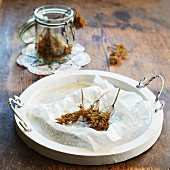 Dried elderflower on a tray and in a glass jar