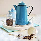 Mallow tea in a teapot with a glass jar and tea sieve