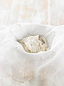 How to prepare vegan macadamia nut cheese: the drained cheese mixture in a muslin cloth
