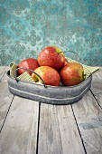 Fresh apples in a metal tray on a wooden table
