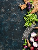 Green and purple basil, red onions and garlic with a mezzaluna and rustic chopping board