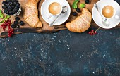 Freshly baked croissants with garden berries and coffee cups on rustic wooden board