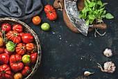 Bunte Heirloom-Tomaten im Korb, Basilikum, Knoblauch und Wiegemesser