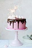 Rosa Geburtstagstorte mit Schokoglasur und Wunderkerzen