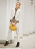 Blonde Frau in beigem Hosenanzug, Schlupfbluse und Stiefeletten hält iPad-Hülle