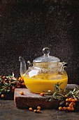 Hot berry sea buckthorn tea drink with apples in glass teapot on clay board