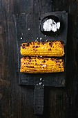 Two grilled bbq sweet corn cobs with sea salt, served on black wood chopping board