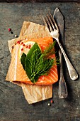 Raw salmon fillet and ingredients for cooking in a rustic style