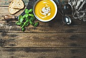 Pumpkin cream soup in bowl with fresh basil, spices and grilled bread slices