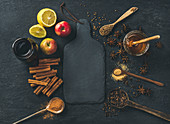 Ingredients for making mulled wine, wine in glass bottle, honey, lemon, apples and spices