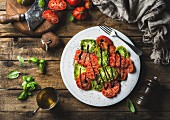 Heirloom tomato salad with olive oil, balsamic vinegar and basil over old rustic wooden background