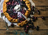 Homemade garden berry galetta or crostata sweet pie with melted vanilla ice-cream