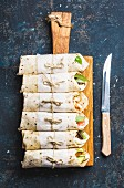 Tortilla wraps with various fillings on wooden serving board and knife over dark blue plywood background