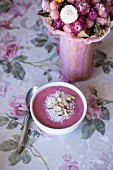 Raspberry smoothie bowl topped with coconut and chopped Brazil nuts on the table