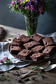 Dark chocolate coconut oil brownies on a plate on rustic wooden table