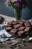 Brownies aus dunkler Schokolade und Kokosöl auf einem Teller auf rustikalen Holztisch