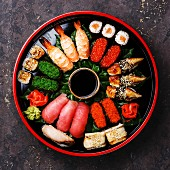 Sushi Set nigiri, rolls, gunkan and sashimi served in traditional Japan black Sushioke round plate