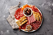 Cold meat plate with prosciutto, salami, ciabatta bread and olives on gray concrete stone background