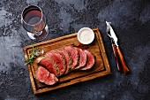 Sliced grilled tenderloin Steak roastbeef and Pepper sauce on wooden cutting board and Red wine