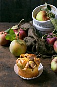 An apple and cottage cheese mini cake in a paper case with fresh apples on a dark wooden surface