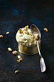 Pistachio ice cream in a tin can with a silver spoon