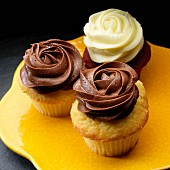 Three cup cakes with dark and white chocolate cream icing
