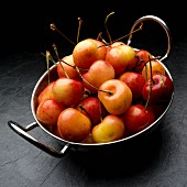 Pale red Rainier cherries in a metal bowl