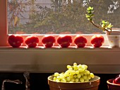 Tomatoes on a sunny windowsill and a ceramic bowl full of grapes in the kitchen