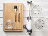 Kitchen utensils: a hand blender, citrus press, measuring cup and cutlery