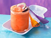 A carrot and mandarin drink with lime juice and figs