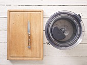 A juicer and a kitchen knife on a wooden chopping board
