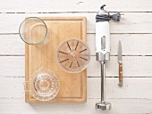 Kitchen utensils: a citrus press, measuring cup, hand blender and knife
