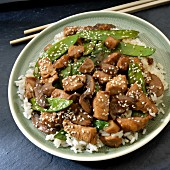 Stir-fried chicken with mangetout on a bed of rice (Asia)