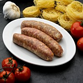 Three fresh Italian sausages (salsiccia) on a plate surrounded by ingredients
