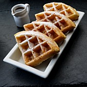 Waffles with icing sugar and syrup