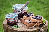 Bread topped with blueberry marmelade on a wooden board in the garden