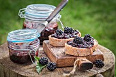 Bread topped with blackberry jam on a wooden board in the garden
