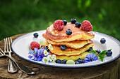 Gestapelte Pancakes mit frischen Beeren und Ahornsirup