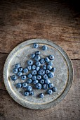 Blueberries on a metal plate (seen from above)