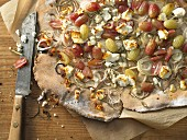 An onion flatbread with grapes, sheep's cheese and rosemary