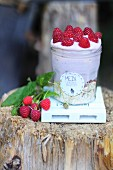 A layered dessert with muesli and raspberry cream in a preserving jar with a deocrative label