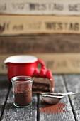 Stillleben mit Kakaopulver in Glasgefäss und Sieb, dahinter Tortenstück und Milchtopf