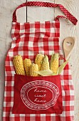 Sweetcorn in the pocket of a red and white checked apron