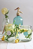 Water aromatised with cucumber, lemon and herbs in glass jars