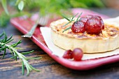 A small cheese quiche with poached red grapes and rosemary