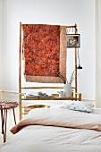 Aufgehängte Quiltdecke über Bambusgestell mit Ablagefläche an Kopfende von Bett